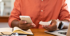 man holding smartphone and piece of paper