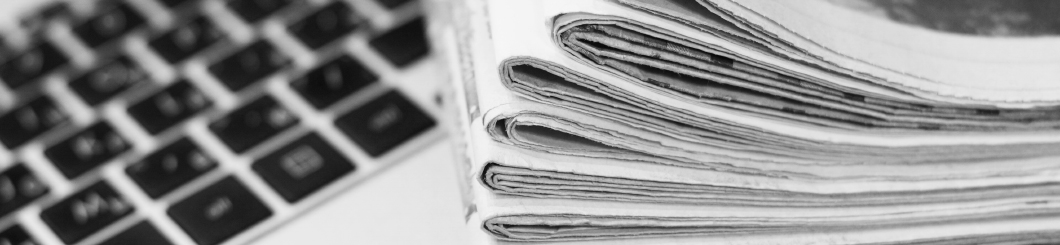 newspapers stacked on laptop
